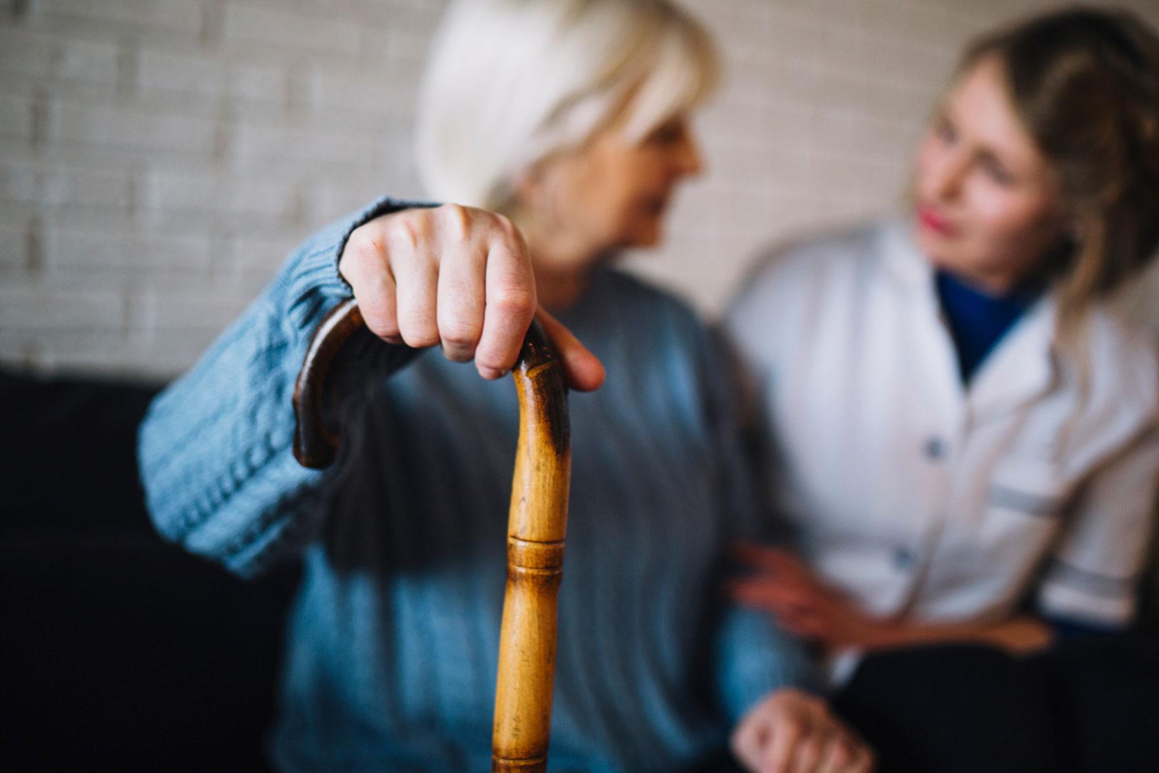 Une femme âgée parle à une infermière.