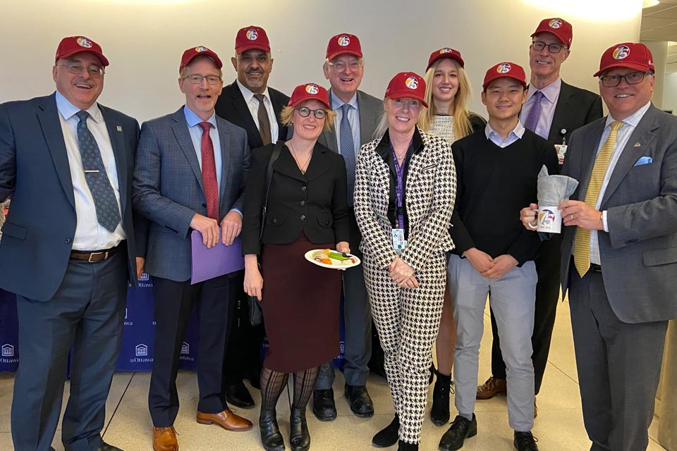 A group of leaders, faculty members and students pose with hats