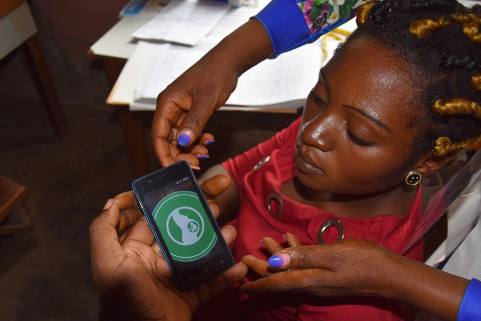 A community health worker trains a woman on how to use an app on her phone.