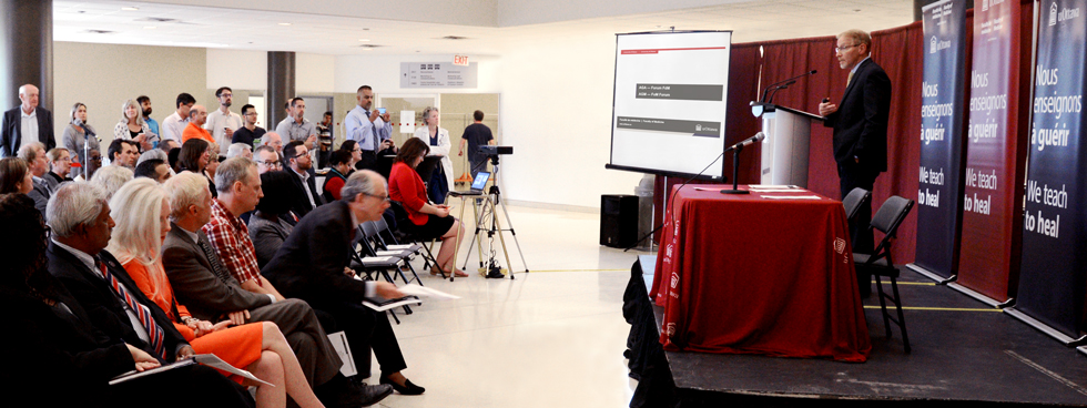 Dr. Bernard Jasmin speaking to the crowd from a stage in the RGN Atrium at the September 15 AGM – FoM Forum