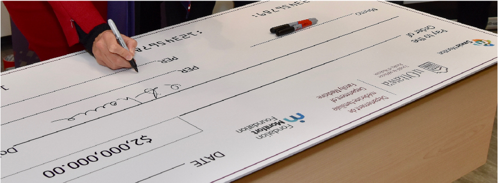 A hand signs an oversized cheque worth $2 million.