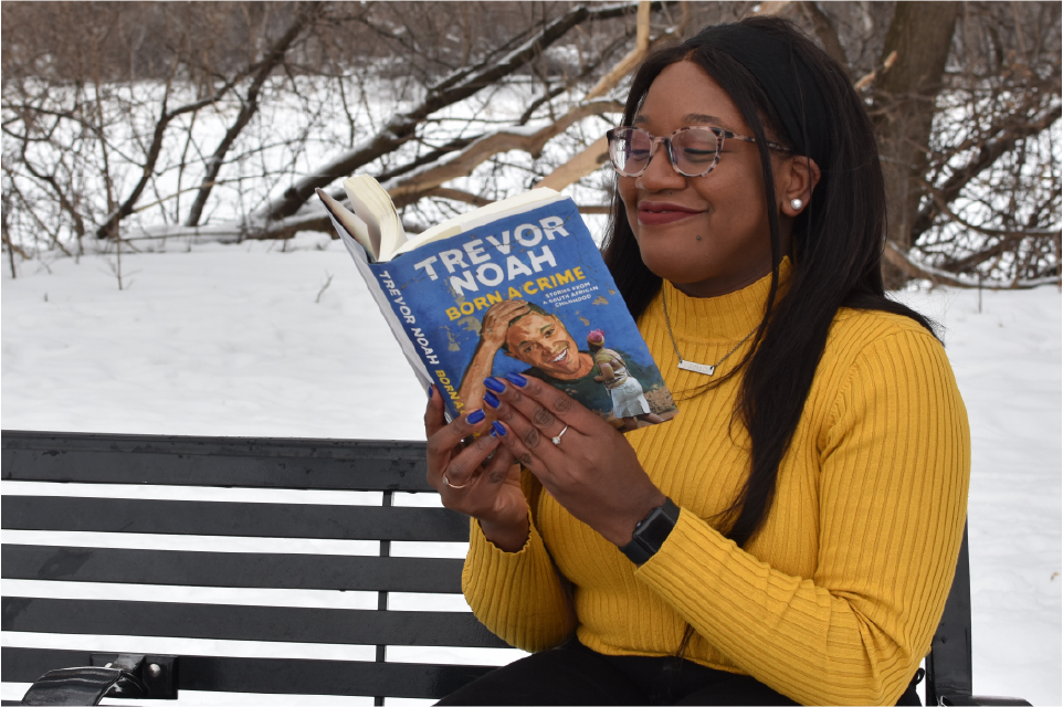 Chisom Okwor sits on a bench reading Born a Crime by Trevor Noah