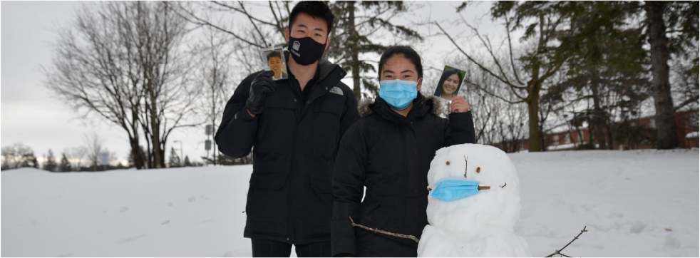 hui Yan and Jason Tran beside a snowman, all wearing masks