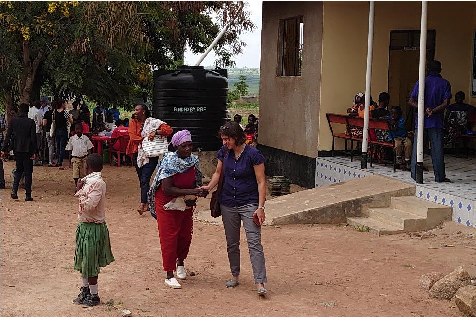 Dr. Manisha Kulkarni speaks with a woman in a Tanzanian village.