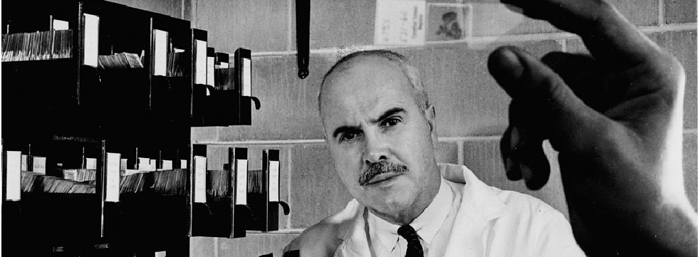 Dr. Desmond Magner, with a microscope slide in the foreground