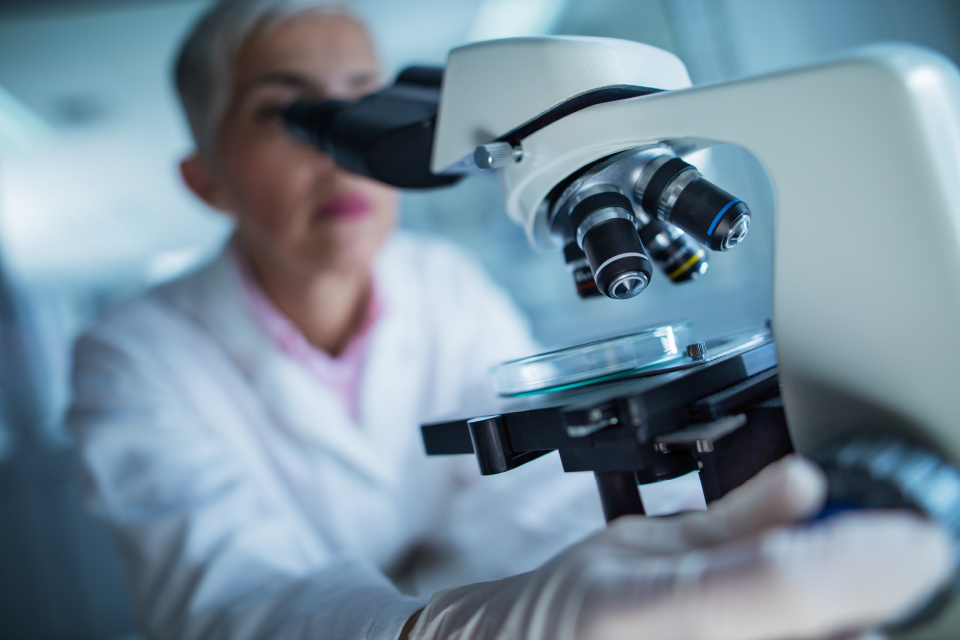a researcher looks through a microscope