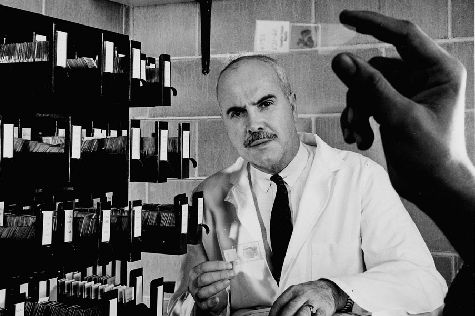 Portrait of Dr. Desmond Magner, with a microscope slide in the foreground