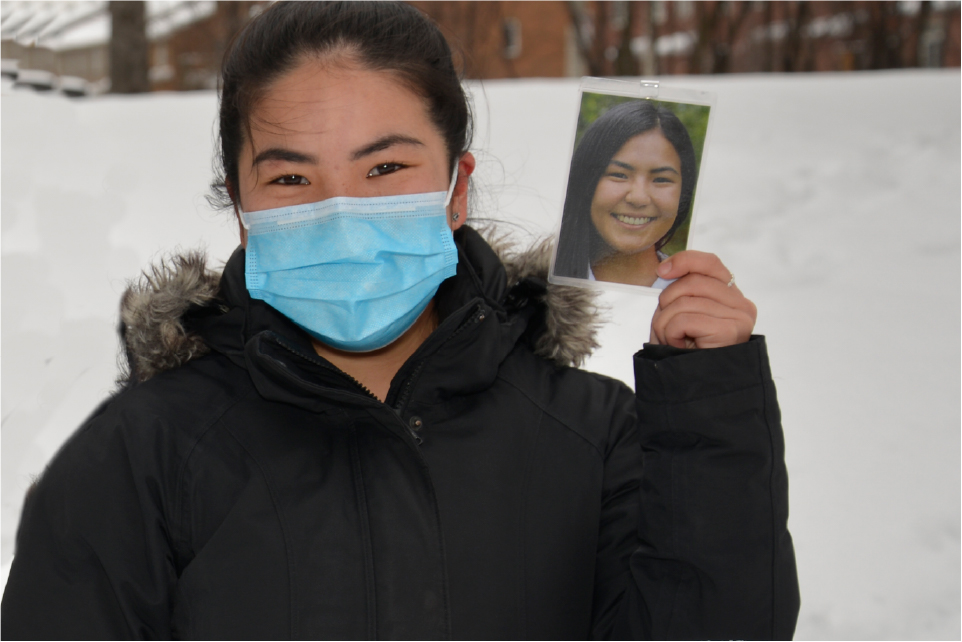MD student Hui Yan wearing a mask and holding up a headshot of herself