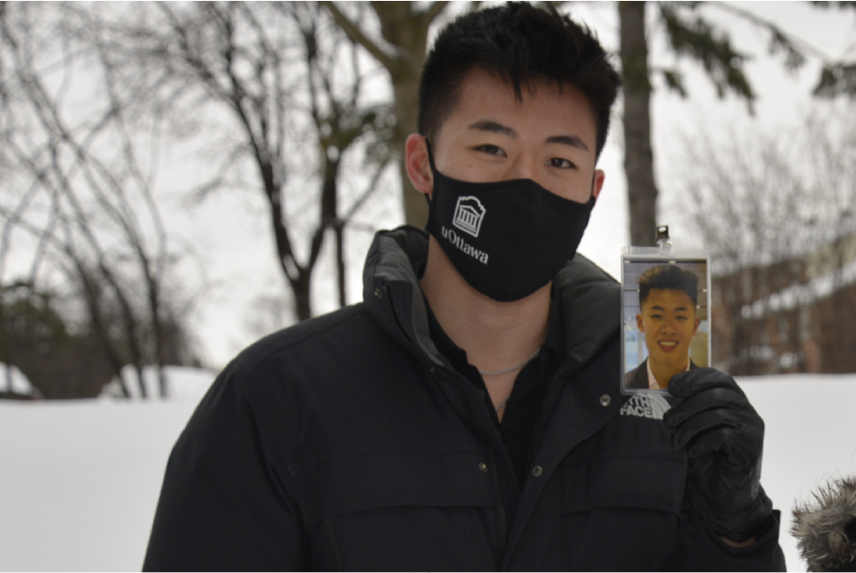md student Jason tran wears a mask, while holding up a photo of himself