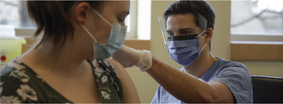 a man administers vaccine to a woman