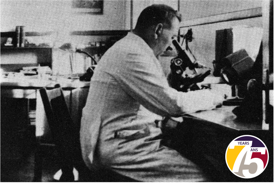 Leonard Belanger peers into a microscope