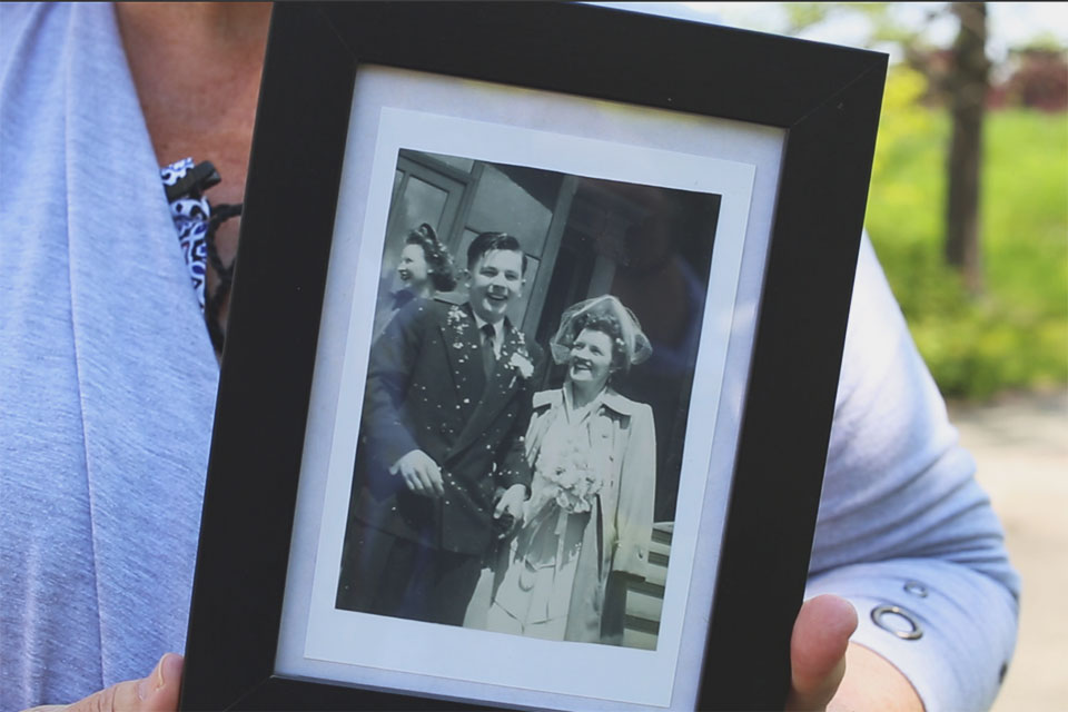 cathy delany holds a photograph of her mother and father on their wedding day.