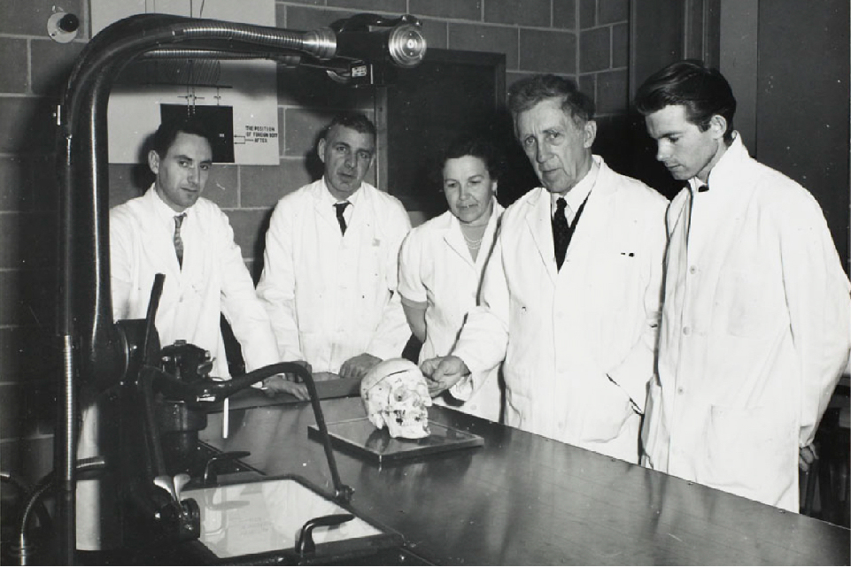 S. Bedok, Charles Marcotte, Mme Victor Linis, Martin Fokkena, standing in front of a lab table with a human skull on it.