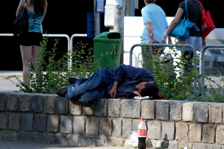 A man lying on a bench outside