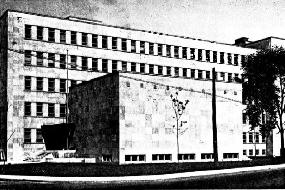 A square concrete building with rows of windows