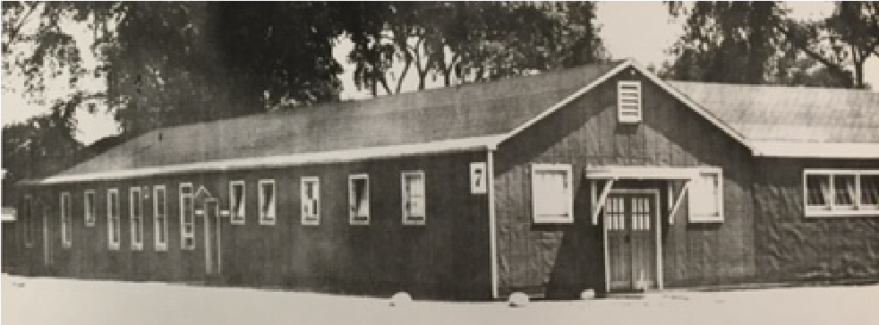 A barracks building, with snow on the roof and icicles hanging from the eaves, stands on snow-covered ground.