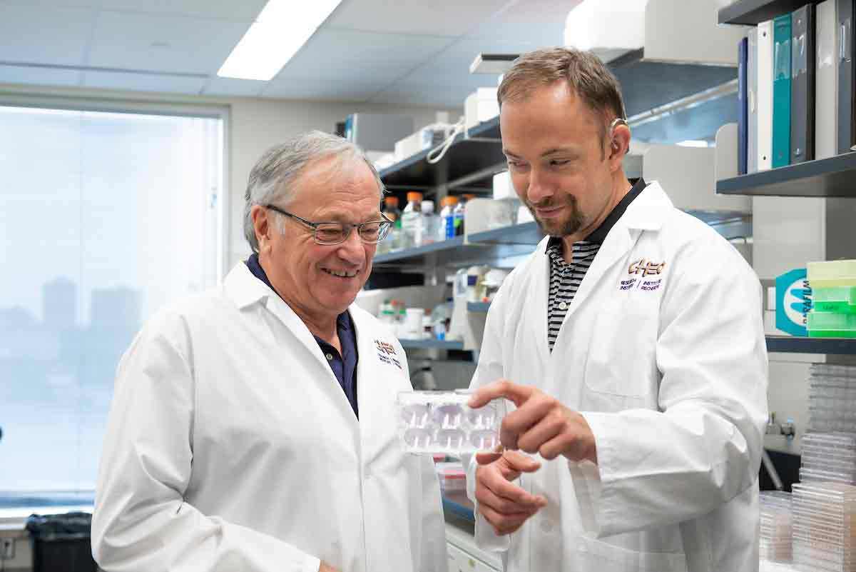 Photo of Dr. Robert Korneluk and Dr. Shawn Beug in the laboratory.