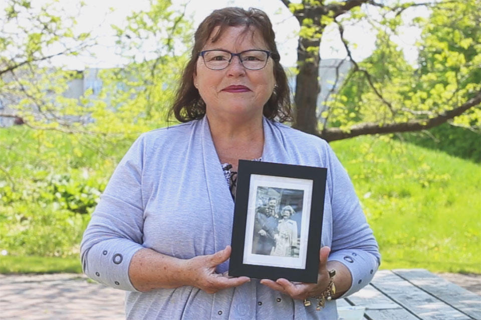 cathy delany holds a photograph of her mother and father