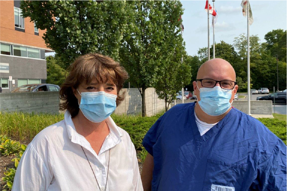 Dr. Marie-Hélène Chomienne stands outside Hôpital Montfort with Paul Shean, a member of the hospital's cleaning staff.