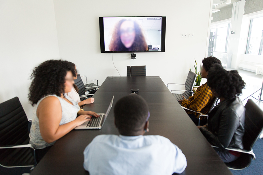 People sitting at a conference table participating in a teleconference