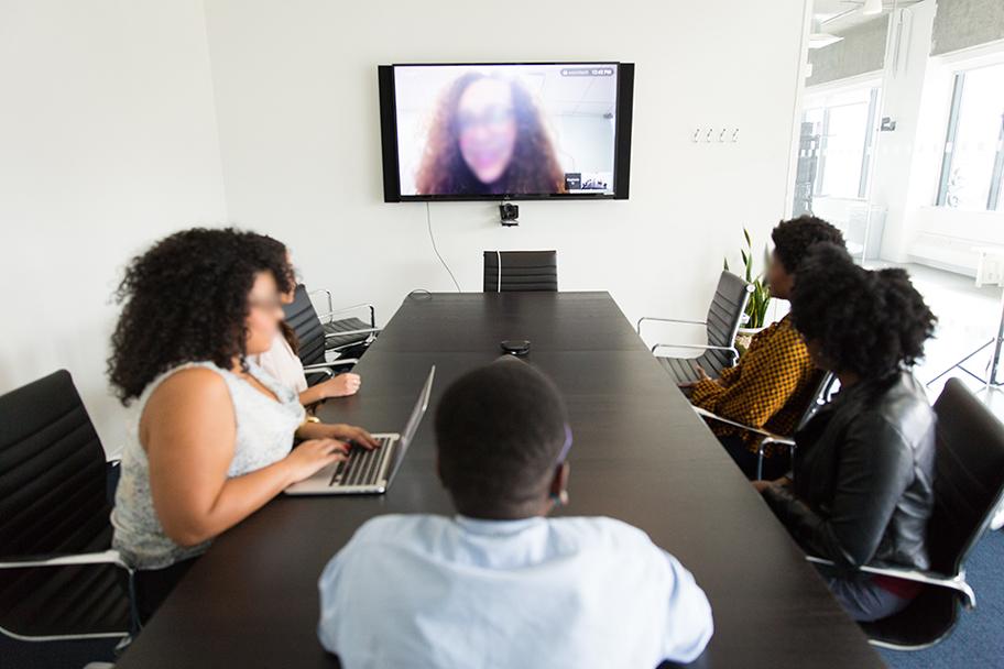 Des gens assis à une table de conférence participant à une téléconférence