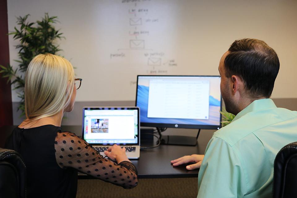 Un homme et une femme lisant des informations sur un ordinateur