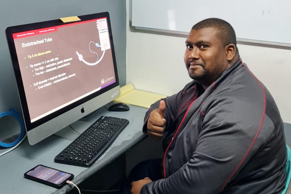 Homme assis devant un ordinateur regardant une photo d'équipement de radiologie