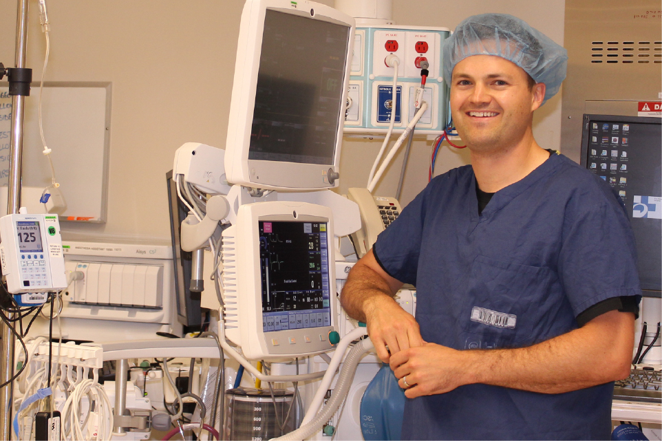 Dr. Daniel McIsaac stands in front of medical machines