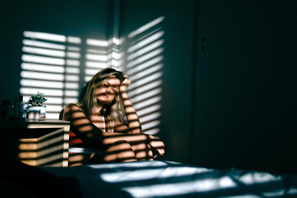 Femme assise dans une pièce sombre