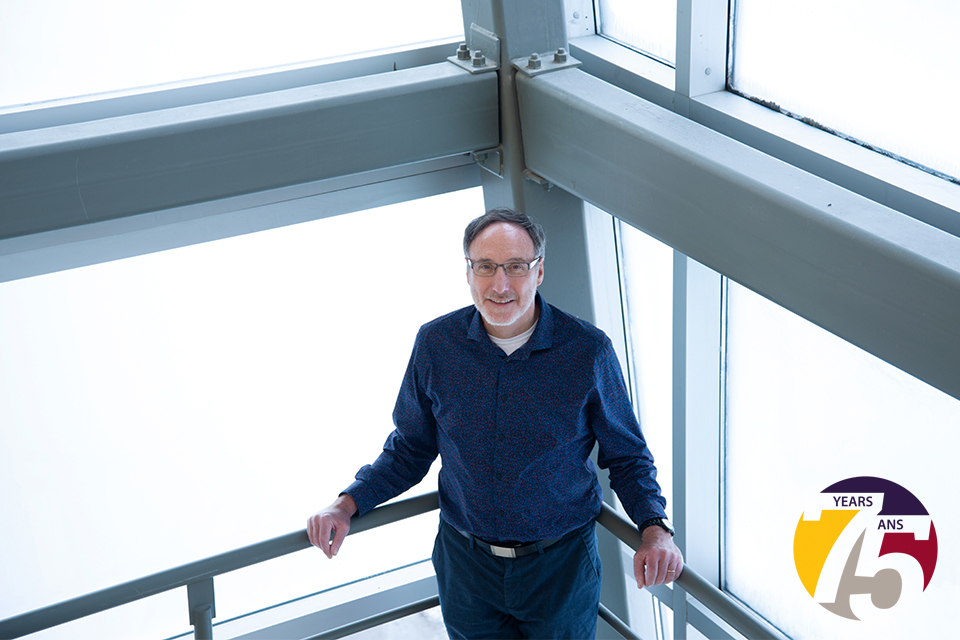 A bird's eye view of a man leaning against a railing in front of a window.