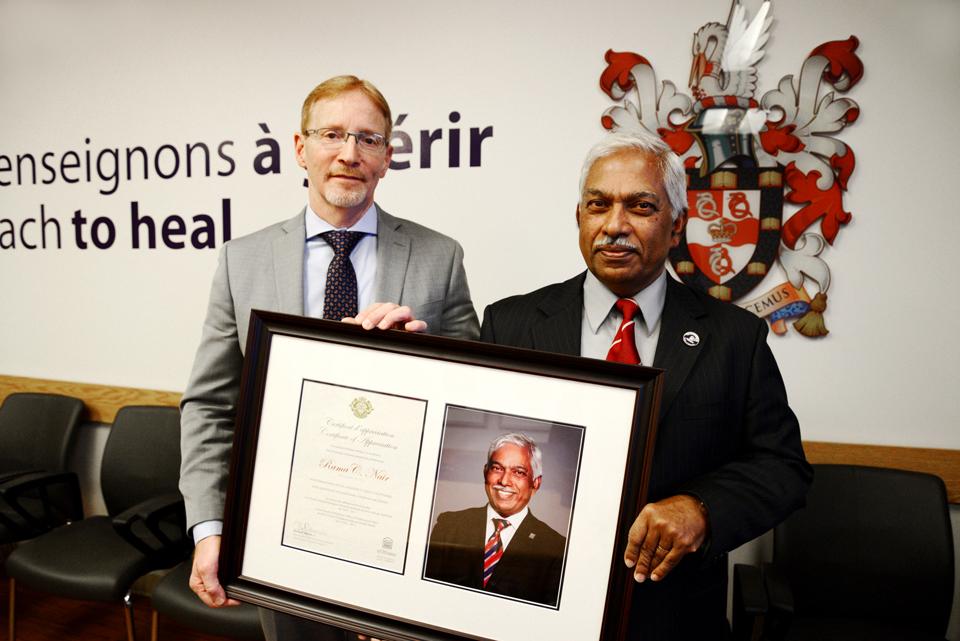 Dr. Bernard Jasmim presents a certificate to Dr. Rama Nair.