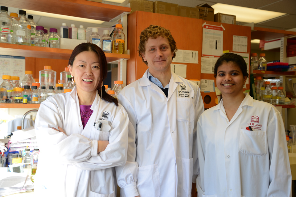Huishan Guo, Dr. Derrick Gibbings and Maneka Chitiprolu standing in a lab together.