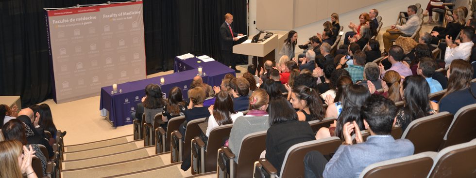 Photo of Dean Bernard Jasmin in front of a full room of people.