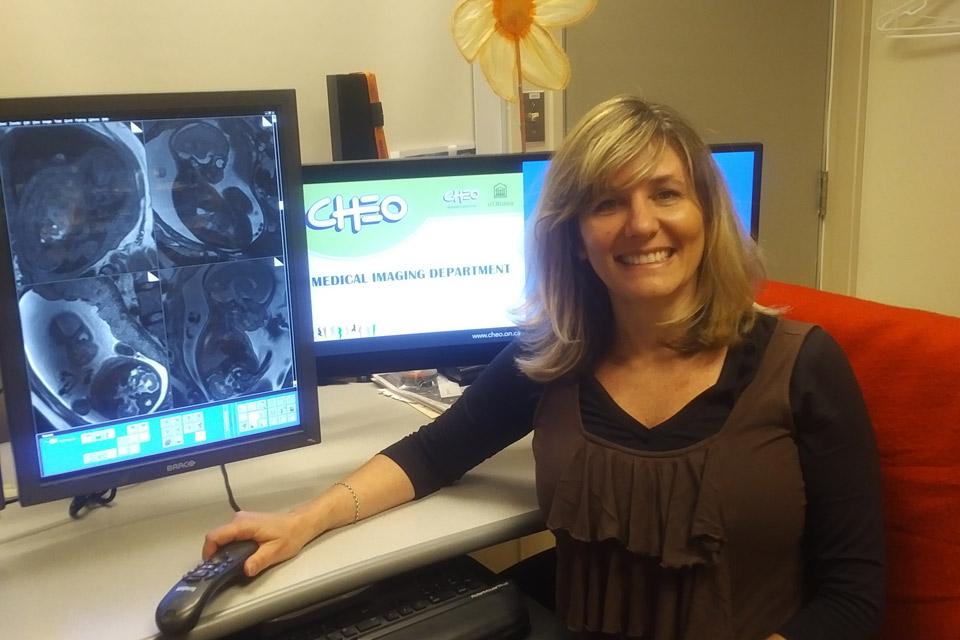 La Dre Elka Miller à son bureau à côté d'un écran d'ordinateur montrant la radiographie d'un fœtus.