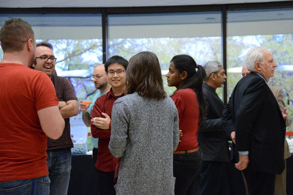 Plusieurs étudiants et professeurs universitaires se tiennent debout dans une grande salle et parlent entre eux.