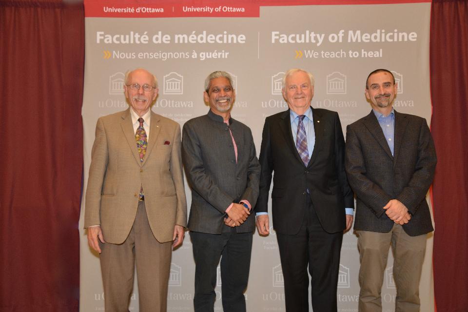 Quatre dignitaires se tiennent debout devant une grande pancarte de l'Université d'Ottawa, Faculté de médecine