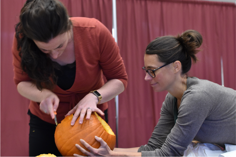 Cynthia Abraham leans over a table, holding a pumpkin, while Kayla Desnoyers cuts into the pumpkin with a carving knife.
