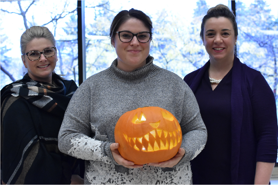 Josée Lortie and Michelle Émard stand on either side of Jenn Therrien, who holds a grinning jack-o'-lantern.