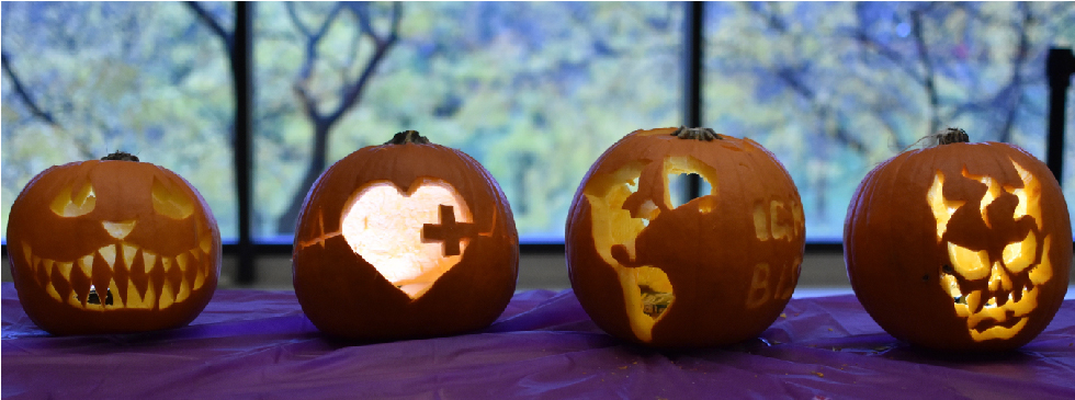 Four carved pumpkins sit in a row on a purple table-cloth in front of a window, with trees in the background.