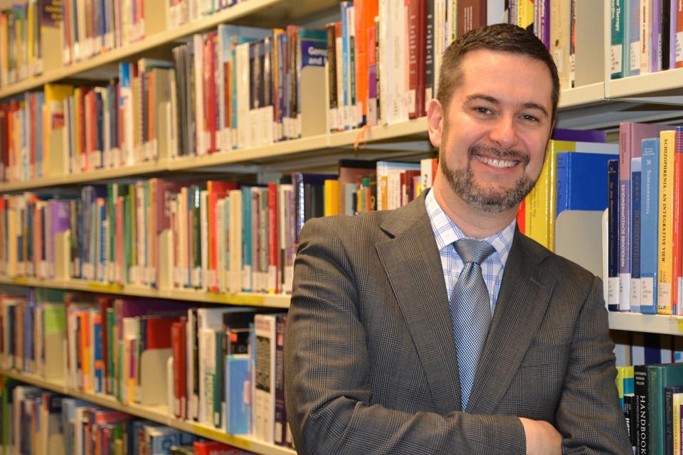 Dr Ian Colman debout dans une bibliothèque.