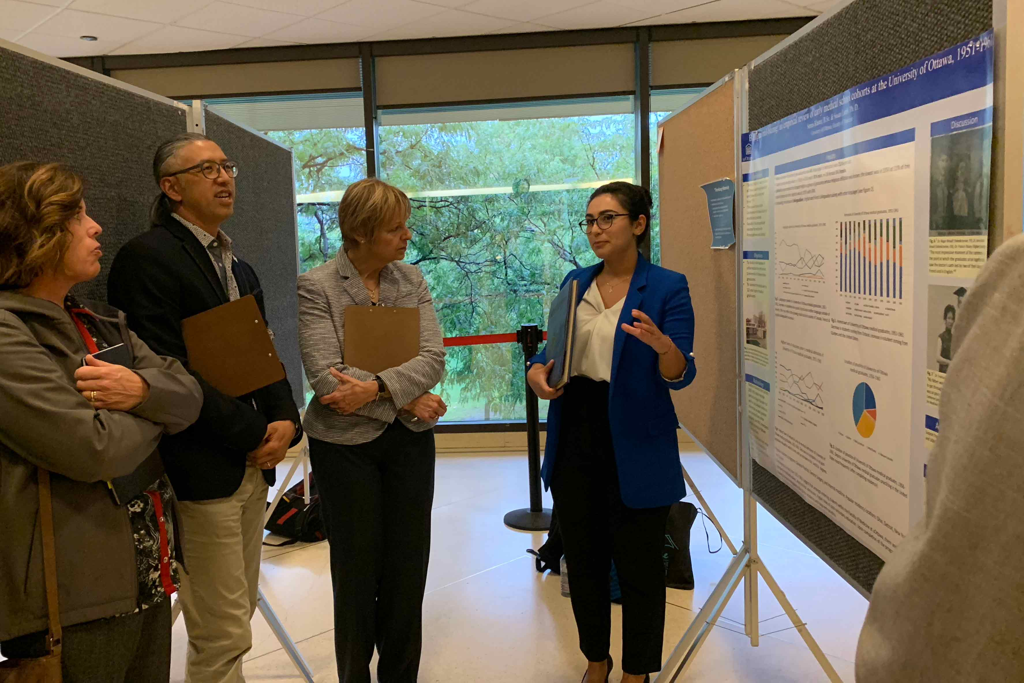 Photo of Serina Khater explaining her poster to three judges.