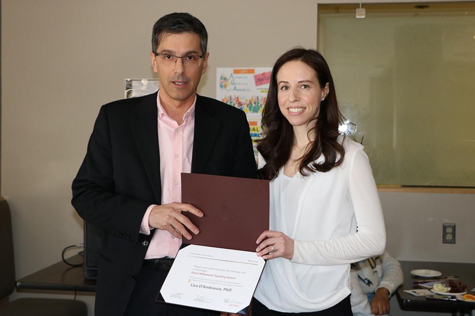 Un professeur reçoit un prix d'un autre professeur.