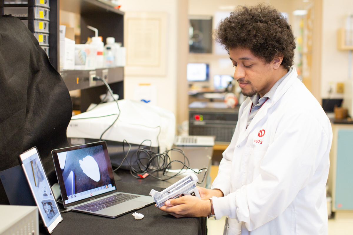 Maxime Comtois-Bona demonstrating the patch-printing device on a tiny 3D-printed heart