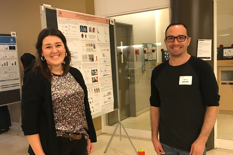 Two people standing in front of a research poster