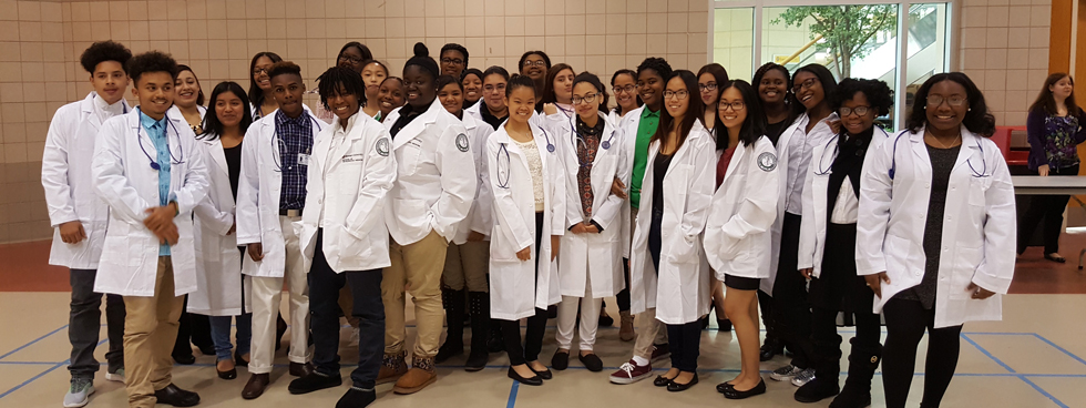 A large group of students poses together in lab coats and stethoscopes.
