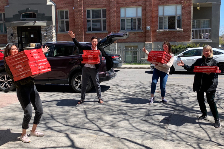 A group of medical students holding boxes of pizza.