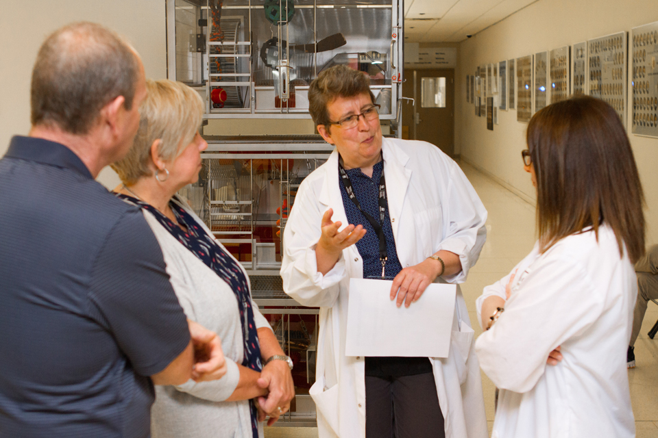 A staff member of the Faculty of Medicine talking to guests.