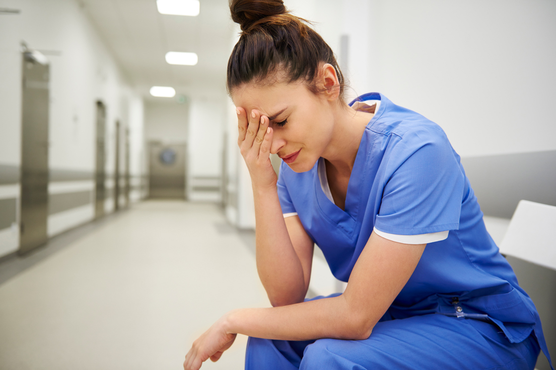 a stressed female doctor sitting in a hospital corridor