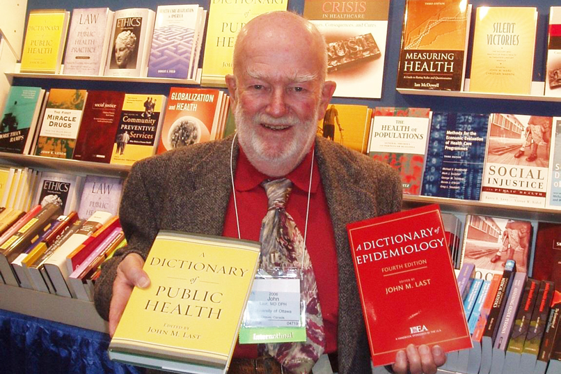 Dr. John Last poses with his dictionaries.