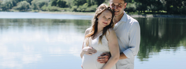 Un homme est derrière sa femme enceinte.